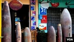 """老挝川圹省首府丰沙湾市内一家名为""""弹坑""""的餐馆,门口装点着不少排除后的炮弹壳。(美国之音朱诺拍摄,2011年2月5日)"""