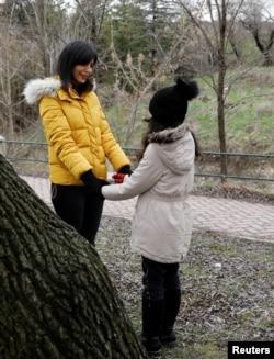 Azam Jangravi bersama putrinya di sebuah taman di lokasi yang tidak diungkap, 7 Februari 2019.