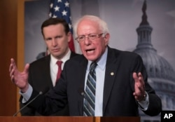 Sen. Bernie Sanders, I-Vt., joined at left by Sen. Chris Murphy, D-Conn., holds a news conference after the Senate passed a resolution he introduced that would pull assistance from the Saudi-led war in Yemen, a measure to rebuke Saudi Arabia after the killing of journalist Jamal Khashoggi, at the Capitol in Washington, Dec. 13, 2018.
