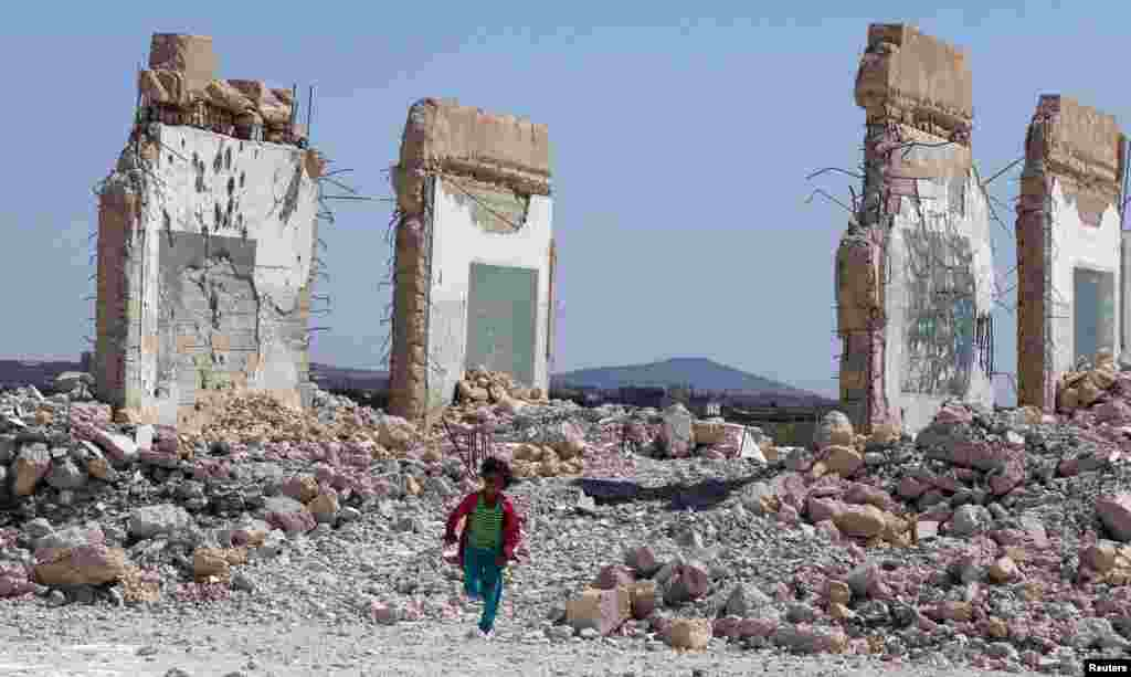 A girl runs near a damaged site in the Quneitra countryside, Syria.