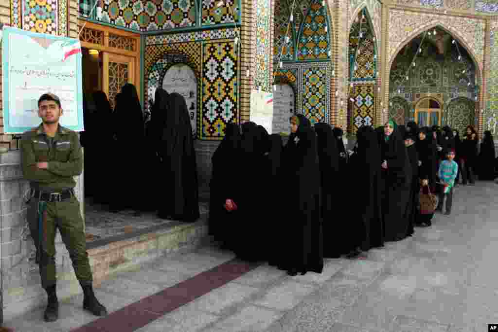 Women stand in line at a polling station during the presidential election in Qom, Iran, June 14, 2013.