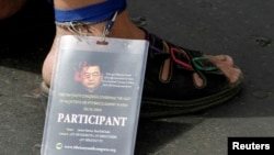 FILE - A Tibetan exile wears a badge on his ankle with a photo of former Chinese president Hu Jintao during a protest against Beijing's policies.
