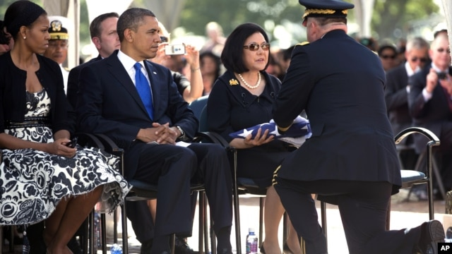 President Barack Obama and First Lady Michelle Obama look on from left as Irene Hirano Inouye, the widow of the late Sen. Daniel Inouye, is given the flag that was draped over her husband's casket during a  memorial service at the National Memorial Cemete