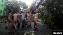 Polisi India dan warga setempat berusaha memindahkan pohon yang tumbang ke jalan akibat angin kencang di Chennai, India, Senin (12/12).