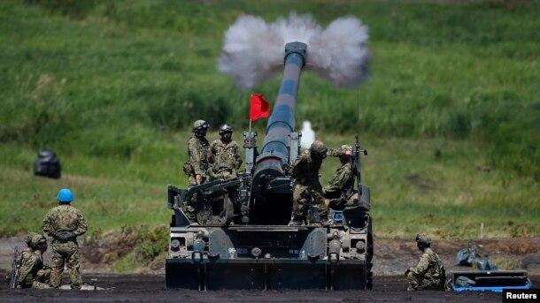 Binh sĩ Lực lượng Phòng vệ Mặt đất Nhật Bản bắn pháo tự hành trong cuộc tập trận thường niên gần núi Phú Sĩ, phía tây Tokyo, ngày 19 tháng 8 năm 2014.