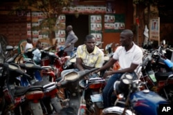 FILE - Supporters of an opposition coalition sit outside a local alliance office in Bamako, Mali.