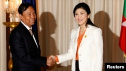 Speaker of Myanmar's Lower House of Parliament Thura Shwe Mann (L) shakes hands with Thailand's Prime Minister Yingluck Shinawatra during his visit to Thailand at the Government House in Bangkok, Sept. 23, 2013.