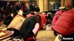 Những cô gái hành nghề mại dâm và khách mua hoa bị bắt trong chiến dịch bài trừ mại dâm tại một khách sạn ở Đông Quan, tỉnh Quảng Đông, ngày 9/2/2014.