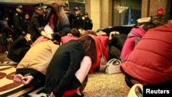 Police conduct a head count of suspects who were detained during a police raid, as part of plans to crackdown on prostitution, at a hotel in Dongguan, Guangdong province, Feb. 9, 2014.