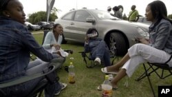 Township residents picnic beside luxury vehicles in Soweto's Thokoza Park. South Africa's black middle class is fueling a consumer boom (File Photo)