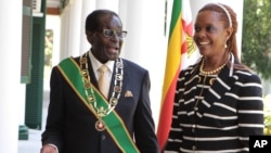 FILE: Zimbabwe President Robert Mugabe stands with his wife Grace, as they pose for a photo at State House in Harare, Oct, 28, 2014.