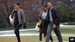 Presiden AS Barack Obama dan putrinya Sasha (tengah) dan Malia, di Gedung Putih saat kembali dari liburan di Hawaii, Januari 2014.