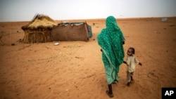 ARSIP – Foto yang dirilis oleh United Nations African Union Mission in Darfur (UNAMID) menunjukkan gambar seorang wanita yang bergandengan tangan dengan anak perempuannya sambil berjalan di kamp pengungsi Zam Zam untuk mereka yang tersingkir di Darfur Utara, Sudan. (foto: AP Photo/UNAMID, Albert Gonzalez Farran)