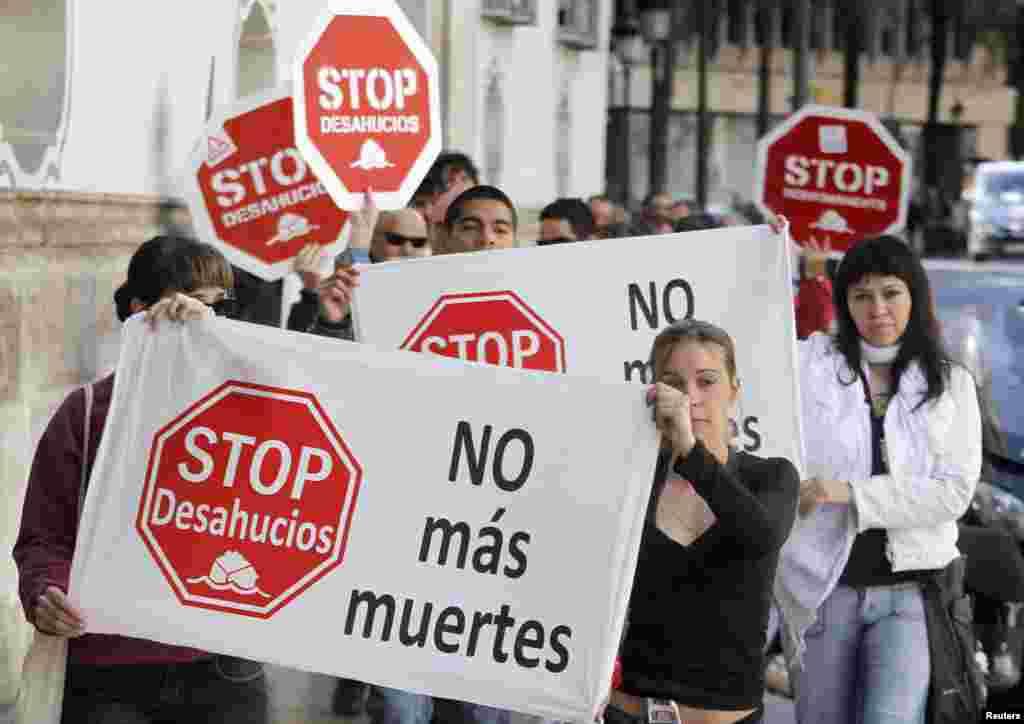 """Những người sắp sửa bị đuổi nhà biểu tình bên ngoài ngân hàng Banesto tại Valencia, Tây Ban Nha. Bích chương, biểu ngữ mang dòng chữ """"Chấm dứt đuổi nhà"""" và """"Không có thêm người chết nữa"""" ý muốn nhắc đến các vụ tự tử vì không trả được tiền vay nợ để mua nhà."""