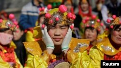 Performers wait for their turn to go onto the stage at the Longtan park as the Chinese Lunar New Year, which welcomes the Year of the Monkey, is celebrated in Beijing, China, Feb. 9, 2016.