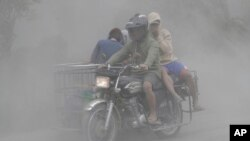 A family rides their motorcycle through clouds of ash as they evacuate to safer grounds as Taal volcano in Tagaytay, Cavite province, southern Philippines on Monday, Jan. 13, 2020. (AP Photo/Aaron Favila)