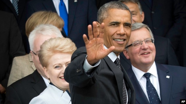 U.S. President Barack Obama, center, waves as he arrives for a group photo during a NATO summit at the Celtic Manor Resort in Newport, Wales, Sept. 4, 2014.
