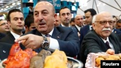Turkey's Minister for Culture and Tourism Nabi Avci and Turkish Foreign Minister Mevlut Cavusoglu attend the International Tourism Trade Fair in Berlin, Germany, March 8, 2017.