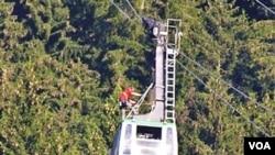 Para petugas membantu penyelamatan 20 wisatawan dari kereta gantung yang macet selama 17 jam lebih di atas Tegelberg, dekat Schwangau, pegunungan Alpen selatan di Jerman (13/8).