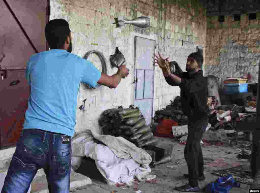 A Free Syrian Army fighter throws a mortar shell to a fellow fighter in Jabal al-Akrad area in Syria's northwestern Latakia province, Nov. 6, 2013.