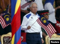 Malaysia's Prime Minister Najib Razak waves a Malaysian national flag during National Day celebrations in Kuala Lumpur, August 31, 2015.
