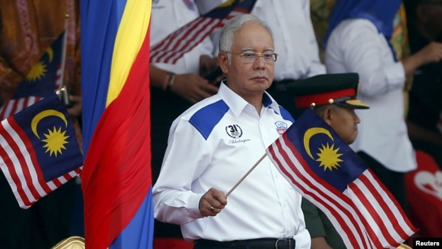 FILE - Malaysia's Prime Minister Najib Razak waves a national flag during National Day celebrations in Kuala Lumpur, August 31, 2015. He denies all allegations of financial wrongdoing in the case brought against him.