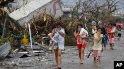 Warga yang selamat dari topan Haiyan di Tacloban, pulau Leyte menutup hidung akibat bau menyengat mayat para korban tewas (10/11).