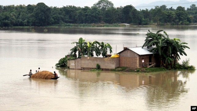 Indian villagers move in a country boat through a flooded village in Morigaon district of northeastern Assam state, India, Monday, Aug. 18, 2014.