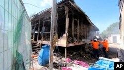 Công nhân dập tắt những ngọn lửa còn cháy âm ỉ sau khi 125 người xin tị nạn nổi loạn tại một trung tâm giam giữ người tị nạn của Úc ở Nauru. (Ảnh chụp ngày 19/7/2013)