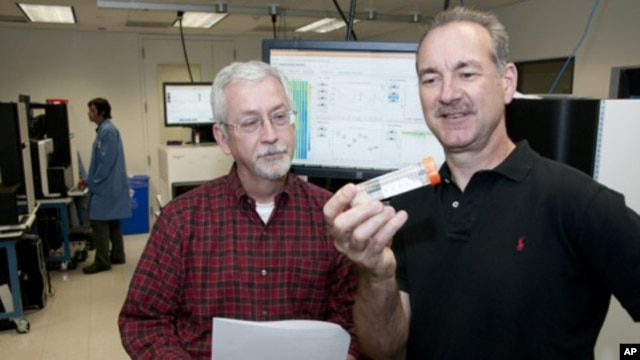 Timothy Ley , MD (left) and Richard Wilson, PhD, looking at a flow cell in the genome sequencing lab. They and their Washington University colleagues have shown the power of sequencing cancer patients' genomes as a diagnostic tool.