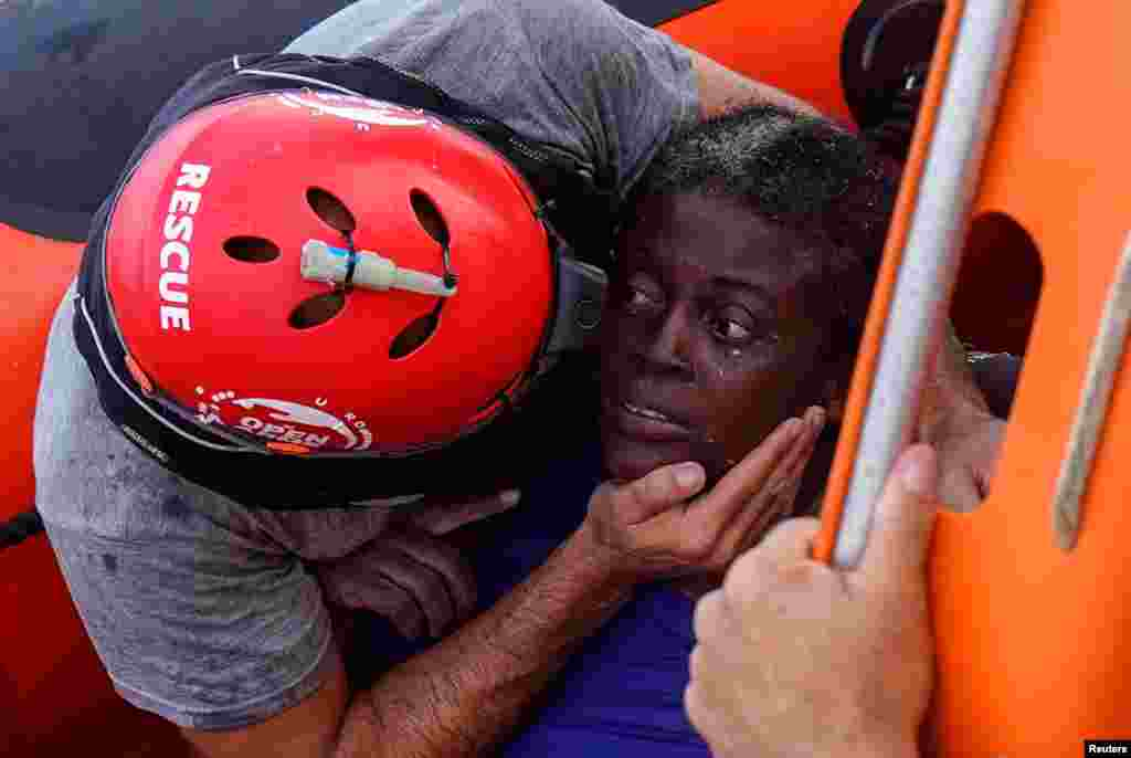 A crew member of the NGO Proactiva Open Arms rescue boat embraces an African migrant in the Mediterranean Sea.