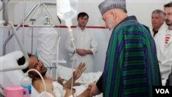Presiden Afghanistan, Hamid Karzai berbicara dengan seorang korban luka-luka dalam serangan pada hari raya Ashura di Kabul.