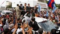 Sam Rainsy, leader of the opposition Cambodia National Rescue Party (CNRP) greets supporters in Phnom Penh, Cambodia, Saturday, July 19, 2014.
