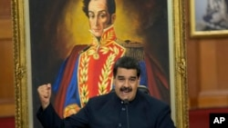 Venezuelan President Nicolas Maduro, shown at the presidential palace in Caracas with a painting of independence hero Simon Bolivar, defends gubernatorial election results at a news conference Oct. 17, 2017.