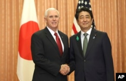 FILE - Japanese Prime Minister Shinzo Abe, right, and U.S. Vice President Mike Pence shake hands prior to a luncheon hosted by Abe at the prime minister's official residence in Tokyo, April 18, 2017.