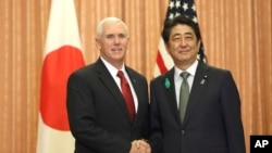 Japanese Prime Minister Shinzo Abe, right, and U.S. Vice President Mike Pence shake hands prior to a luncheon hosted by Abe at the prime minister's official residence in Tokyo, April 18, 2017.