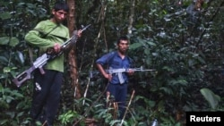 FILE - Members of Peru's Shining Path terrorist group are seen in a remote jungle region in southern Peru, Cuzco. Peruvian special forces rescued 26 children and 13 women, some of whom had been held captive for three decades, when they raided a southeastern jungle camp of the left-wing rebel group.