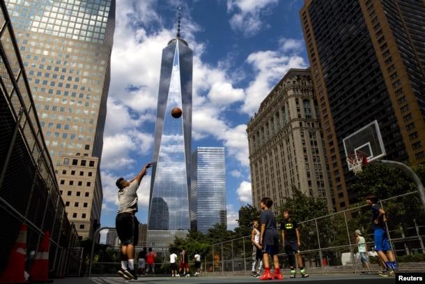 One World Trade Center towers over lower Manhattan as children play basketball in New York August 26, 2015. REUTERS/Brendan McDermid