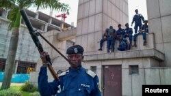 Des policiers congolais assis sur le bâtiment de la gare centrale, à Gombe, Kinshasa, en RDC, le 19 décembre 2016.