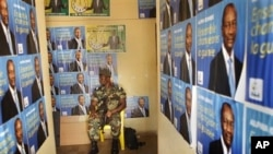 A soldier sits amidst election posters of Presidential candidate Alpha Conde in the entrance of the Guinean People Rally (RPG) headquarters in Guinea's capital Conakry Saturday 18 Sept. 2010