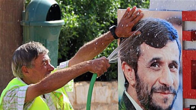 A Lebanese worker washes a portrait of Iranian President Mahmoud Ahmadinejad, at a border park in the village of Maroun el-Rass on the Lebanon-Israel border, Lebanon, 4 Oct 2010