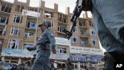 Seorang polisi Afghanistan melintasi bangunan yang digunakan sebagai basis pertahanan militan dalam serangan 18 jam di Kabul (16/4).