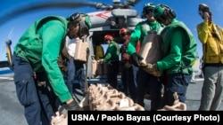 15일 미 항공모함 조지워싱턴호 선원들이 태풍 피해지역에 전달할 구호물자를 시호크 헬리콥터에 싣고 있다.