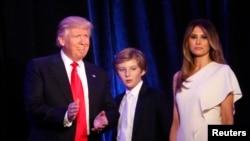 Presiden terpilih AS, Donald Trump, bersama putranya Barron dan istrinya Melania di Manhattan, New York (9/11). (Reuters/Carlo Allegri)