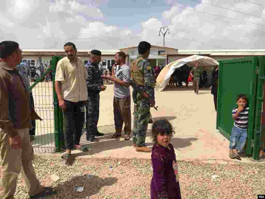 មនុស្សម្នាឈរតម្រង់ជួរ ខណៈដែលកងកម្លាំងសន្តិសុខយាមតំបន់នោះ នៅខាងក្រៅស្ថានីយបោះឆ្នោតនៅក្នុងជំរំជនភៀសខ្លួន Khazir ខាងកើតក្រុង Mosul ប្រទេសអ៊ីរ៉ាក់ កាលពីថ្ងៃទី១២ ខែឧសភា ឆ្នាំ២០១៨។