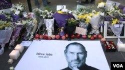 Buah apel segar dan bunga tanda dukacita diletakkan bersama poster Steve Jobs di luar gerai Apple di Beijing, Tiongkok (6/10).