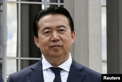 FILE - President Meng Hongwei poses during a visit to the headquarters of International Police Organisation in Lyon, France, May 8, 2018.