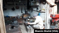 درہ آدم خیل میں ایک کاریگر بندوق بنانے میں مصروف ہے۔
