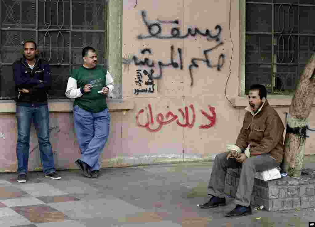 Egyptian men stand near writing on a wall in Arabic that reads down with the leader's rule, no to the Muslim Brotherhood in Tahrir Square in Cairo, December 9, 2012.