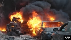 Flames engulf a vehicle following a car bomb blast along al-Khudary Street in the Karm al-Loz neighborhood in the central Syrian city of Homs, April 9, 2014.